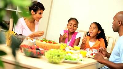 stock-footage-young-african-american-family-sitting-at-the-table-sharing-a-healthy-lunch-together-at-home