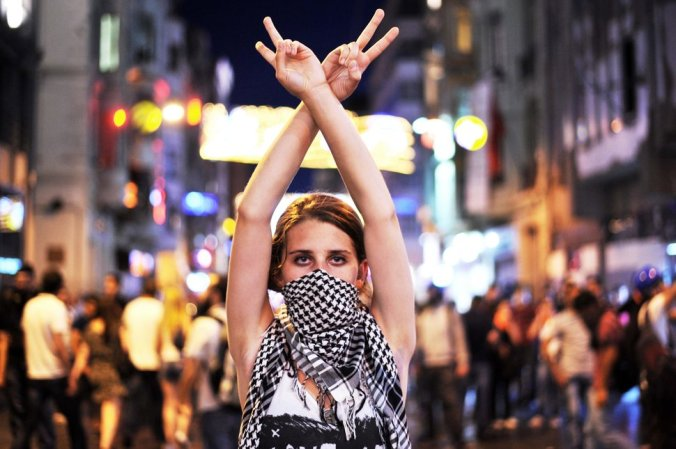 An anti goverment protester flashes a victory sign during the clashes between protestors and riot police on Taksim square in Istanbul on June 22, 2013. Turkish police used water cannon today to disperse thousands of demonstrators who had gathered anew in Istanbul's Taksim Square, calling for the resignation of Prime Minister Recep Tayyip Erdogan. AFP PHOTO / OZAN KOSE (Photo credit should read OZAN KOSE/AFP/Getty Images)