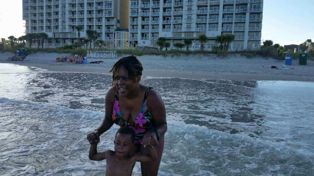 Mommy and D jumping the waves