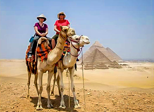 two-female-tourists-riding-camels-at-the-pyramids-of-giza-cairo-egypt